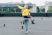 pohled na ženu ve žlutém kabátku si zahrává s mužem na střeše