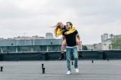 přitažlivá žena a pohledný muž s úsměvem a hravou na střeše