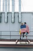 Hátulnézet a nő és az ember amerikai zászló a tetőn