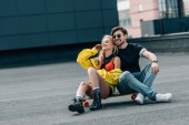 atraktivní žena a pohledný muž v brýlích, které sedí na skateboard
