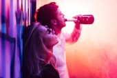 attractive and blonde woman with closed eyes and handsome man drinking champagne
