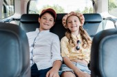 selective focus of happy sister and brother smiling while sitting in car