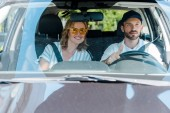 Fotografie selective focus of man driving car near attractive woman