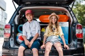 Fotografie happy sister and brother sitting on car trunk and looking at camera