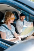 Fotografie selective focus of smiling woman in sunglasses looking at map in car near man