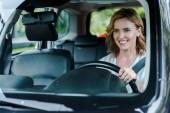 Fényképek célzott fókusz pozitív nő gazdaság kormánykerék és a vezetési autó