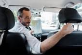Selektiver Fokus eines bärtigen Mannes, der im Auto sitzt und Landkarte hält