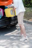 oříznutý pohled člověka stojícího blízko vozu a umístění zavazadla do kufru auta