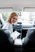 Fényképek középpontjában a mosolygó nő gazdaság térképe az autóban