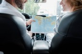 cropped view of happy man and woman holding map in car