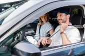 selective focus of cheerful bearded man fastening seat belt near attractive woman in car