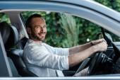 selektivní zaměření šťastného vousatého muže, který se usmívá a dívá se na kameru při jízdě autem