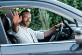 selective focus of happy man driving car and waving hand