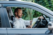 selective focus of bearded man driving car and looking at map