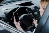 Fotografie oříznutý pohled ženy přidržením telefonu Smartphone s prázdnou obrazovkou v autě
