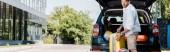 panoramatický záběr veselého vousatého muže v čepici stojící nedaleko zavazadel a auta