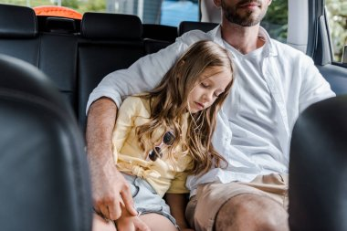 cropped view of father sitting in car near cute daughter with closed eyes