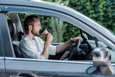 Selective focus of bearded man drinking coffee to go in car stock vector