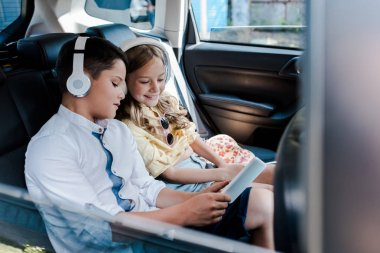 selective focus of happy kids listening music in headphones while looking at smartphone in car