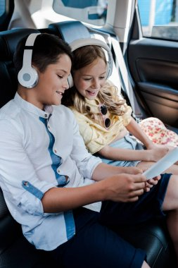 selective focus of cheerful kids listening music in headphones while looking at smartphone in car