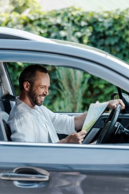 Selective focus of happy driver sitting in car and looking at map stock vector