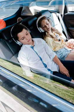 selective focus of cute children in headphones sleeping in car