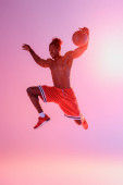 Photo handsome, muscular african american sportsman in red shorts jumping while playing basketball on pink and purple gradient background
