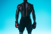 back view of muscular african american sportsman in shorts and boxing gloves on blue background