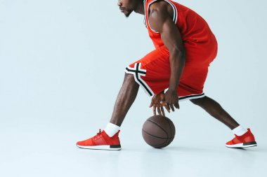 cropped view of african american sportsman in red sportswear playing basketball on grey background