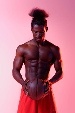 Shirtless, muscular african american basketball player holding ball on pink background with gradient stock vector