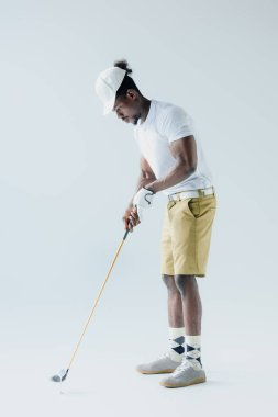 handsome african american sportsman playing golf on grey background