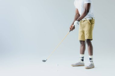 cropped view of african american sportsman in shorts playing golf on grey background