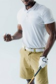 partial view of african american golf player holding ball isolated on grey