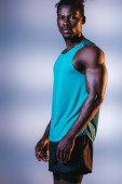 handsome, athletic african american sportsman looking at camera on grey and blue background with lighting