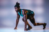 Fotografie atletický afroamerický sportovec stojící v počátečním postavení na šedém pozadí s osvětlením