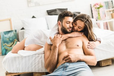 young girl lying in bed and hugging man while guy sitting on floor near bed