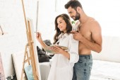 Fotografie sexy man standing behind girlfriend while girl drawing with brush