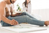 cropped view of man drawing with brush while sitting on floor and girl sitting in bed