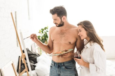 Sexy young man drawing while girl standing with wine and looking at painting stock vector