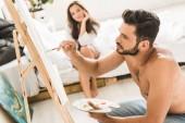 Fotografie Selektiver Fokus von sexy hemdlosen Mann zeichnen und Mädchen im Bett sitzen