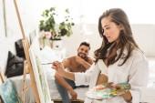 Fotografie selektiver Fokus des sexy Mädchens in weißer Unterwäsche und Hemdzeichnung, während der hemdlose Mann lächelt und im Bett sitzt