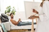 selektivní zaměření člověka ležícího v posteli vínem a děvčetem s kartáčem