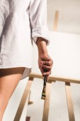 Fotografie low angle view of girl holding paintbrush while standing near easel