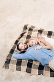boldog pár fekvő együtt csukott szemmel kockás takaró a homokos strandon