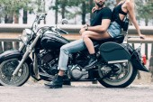 ostříhané zobrazení mladého páru motorkářů na černém motocyklu na silnici