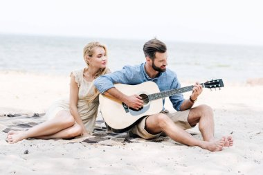 beautiful young barefoot woman sitting on blanket with boyfriend playing acoustic guitar at beach near sea