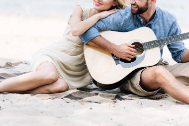 cropped view of beautiful young couple sitting on blanket with acoustic guitar at beach near sea