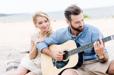 young blonde barefoot woman sitting on blanket near boyfriend with acoustic guitar at beach near sea