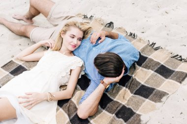 young couple lying together on checkered blanket at sandy beach