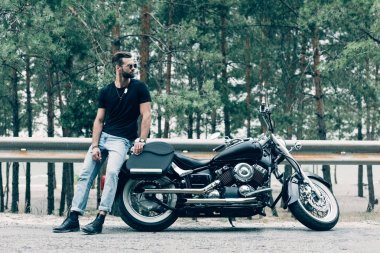 handsome motorcyclist in sunglasses standing near black motorcycle on road near green forest